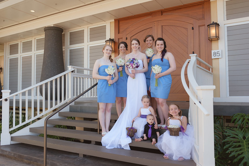 The bridesmaids and flower girls pose with the bride at sugar beach events building in Maui, Hawaii.