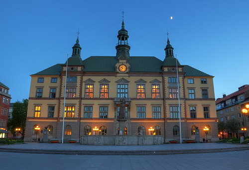 flowers trees windows sculpture building clock fountain lines architecture night square exterior sweden dusk cityhall steps bikes bicycles litter clear sverige hdr crooked eskilstuna stadshuset halfmoon flagpoles fristadstorget emilbefwe