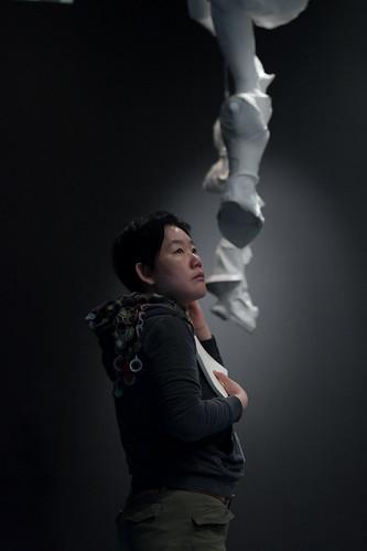 吊るされた彫刻を見上げて展示をチェックするアーティスト