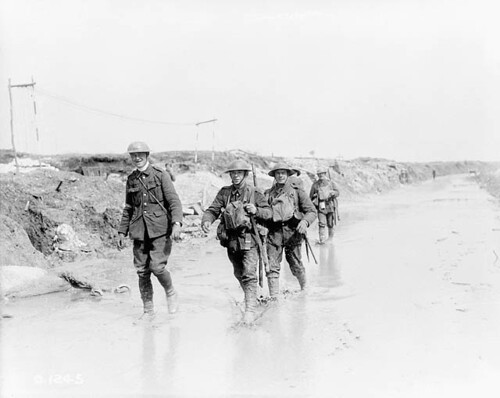 Happy Canadians wading through muddy road. April, 1917 / Soldats canadiens marchant à travers le chemin boueux