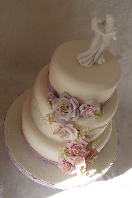 Floral cascade 3 tier wedding cake with lace banding