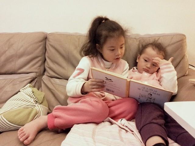 姊姊講故事給妹妹聽。