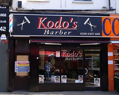 "A single terraced shopfront with a fully glazed frontage.  The sign above reads ""Kodo's Barber"" in white-and-red text on a black background.  The non-glass parts of the frontage are also black.  Headshots of young white and black men are displayed along the bottom of the shop window."