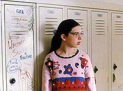 Bespectacled girl looking away wearing a flashy knitted sweater.