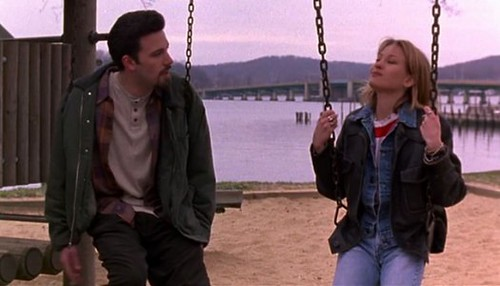 A man and a woman sit on a swing set on the beach. The sky is overcast and the coloring is grey and bleak. Both the man and the woman are wearing several layers of casual clothing. They face each other, in conversation.