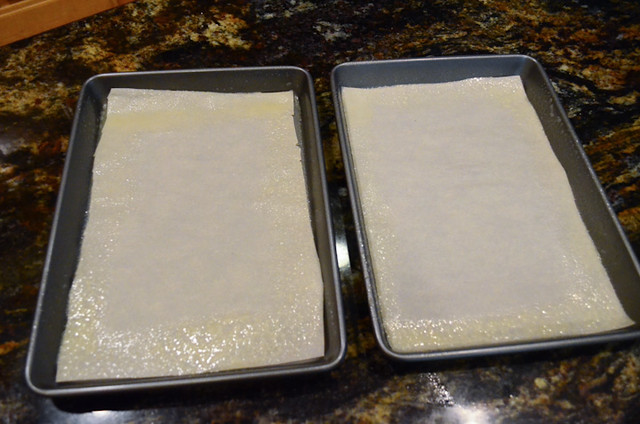 Two baking sheets lined with parchment paper that have been sprayed with cooking spray around the edges.