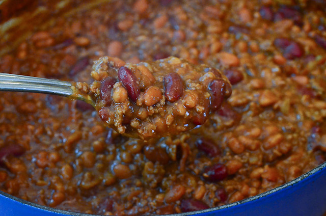 A spoon lifts some of Ryan's Favorite Bean recipe from the Dutch oven.