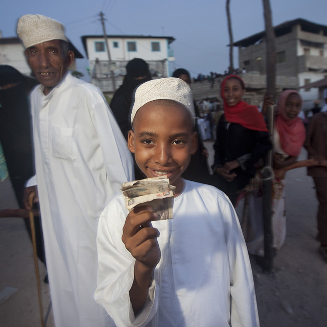 Kofia Headed Young Boy Brandishing His Reward: Banknote In Lamu, Kenya
