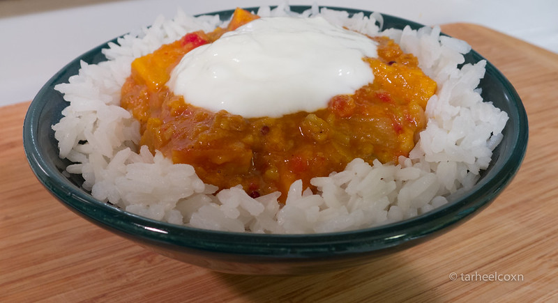 bowl of Sambar over rice with yoghurt on top