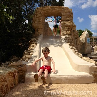 Jasper on the water slide at Quarry Splash Pad in Leander, TX