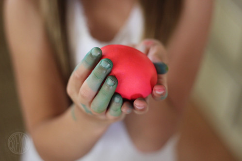 a girl holding a dyed egg in her hands