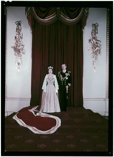 Queen Elizabeth II, wearing a crown and a white fur-trimmed cloak, next to Prince Philip, in uniform, ca. 1950 / La reine Elizabeth II, portant une couronne et une mante garnie de fourrure blanche, et le prince Philip, en uniforme, vers 1950