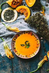 Homemade pumpkin soup on rustic wooden table