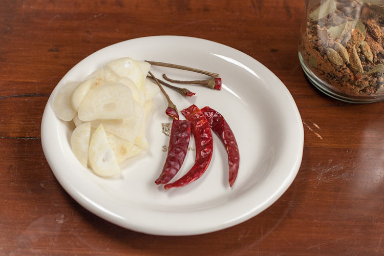 Garlic slices, dried peppers with stems removed, and homemade pickling spice