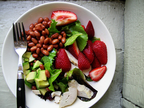 green salad with chicken, red beans, avocado, and strawberries