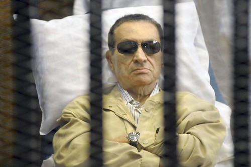 Egypt's ex-President Hosni Mubarak lays on a gurney inside a barred cage in the police academy courthouse in Cairo, Egypt, Saturday, June 2, 2012.
