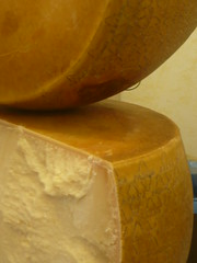 carving(0.0), produce(0.0), yellow(1.0), food(1.0), dairy product(1.0), parmigiano-reggiano(1.0), cheese(1.0),