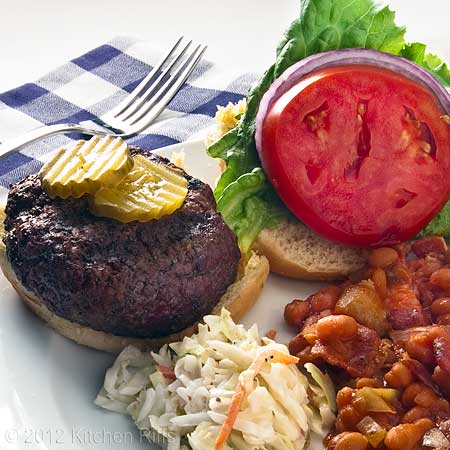 Grilled Hamburger, Bun, and Garnish on Plate with Baked Beans and Cole Slaw