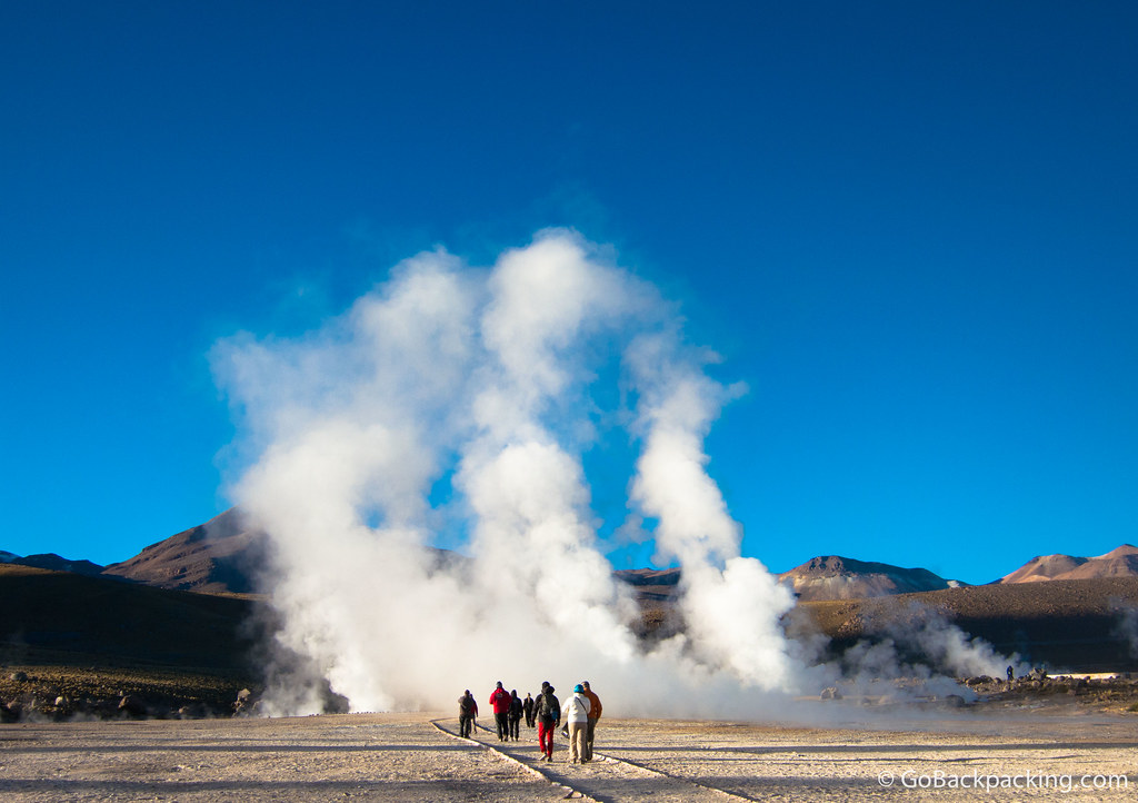 Tourists walk towards one of the field's largest geysers