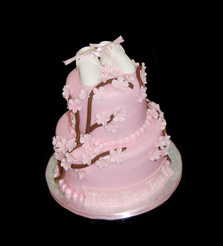Two tiered cake iced with light pink buttercream with cherry blossom