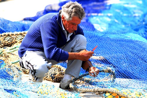 fisherman repairing his fishing net