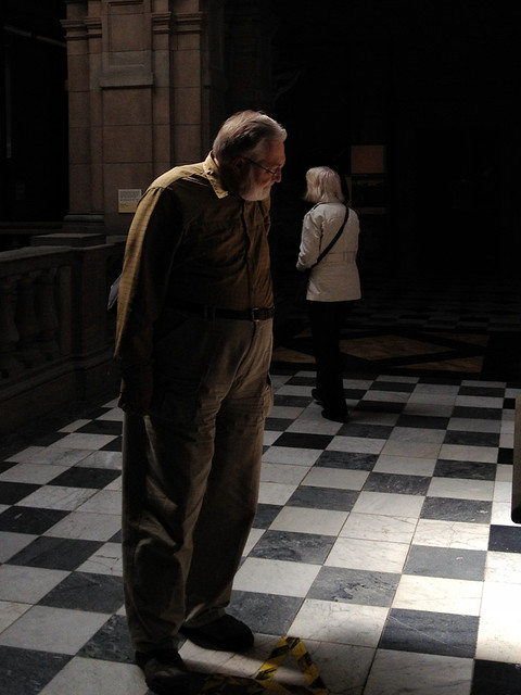 iamge fo two folk inside Kelvingrove art gallery. They are bathed in warm soft light while around them is dark shadow