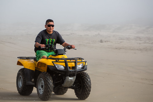 male youth drives an illegal Off Road Vehicle (ORV) All Terrain Vehicle (ATV) on beach
