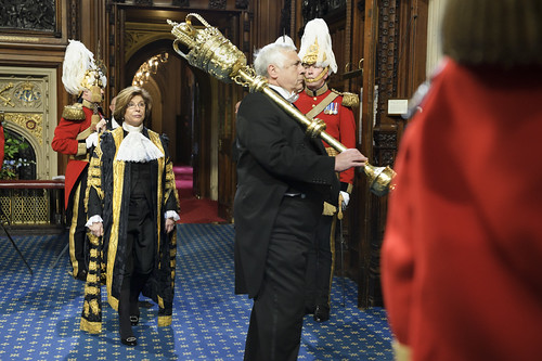 The Lord Speaker, accompanied by the mace and doorkeepers, makes her way to Sovereign's Entrance to await the arrival of the Queen
