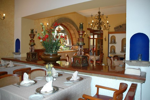 Angel candle holders, flower arrangement, chandelier, volcanic stone arch, place settings, set up tables, dining room, Guadalajara, Jalisco, Mexico