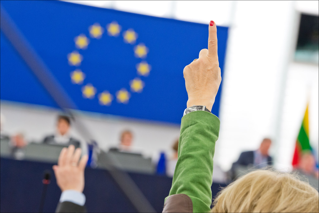 A finger and a hand going up, indicating a positive vote