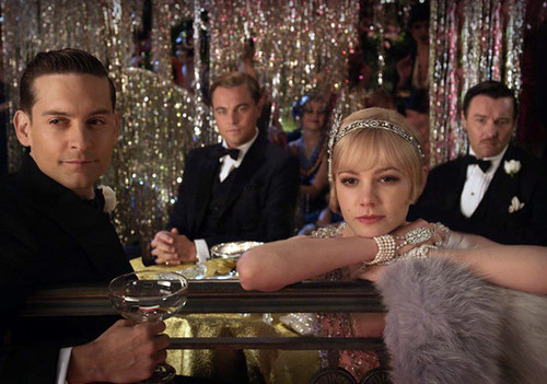 Screen shot from the Great Gatsby trailer, showing the four leads sitting around a table staring outward.