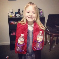 Emma modeling her school project. A scarf (she knit) with cup holders
