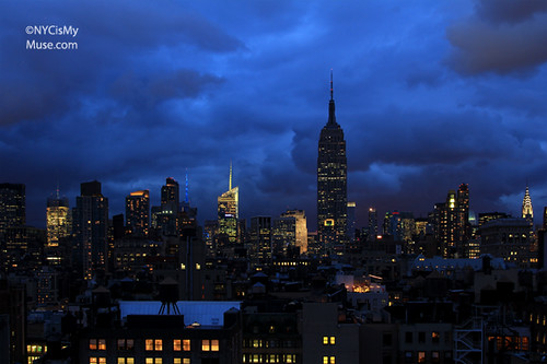 Empire State Building, NYC skyline under dark presunset clouds