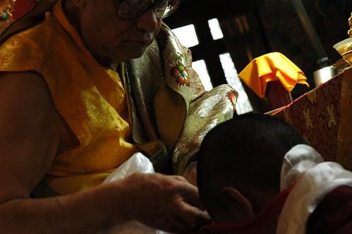 His Holiness Jigdal Dagchen Sakya tying a red blessing cord on a monk, wearing traditional silk garments, khata, Sakya Lamdre, Tharlam Monastery of Tibetan Buddhism, Boudhanath, Kathmandu, Nepal by Wonderlane