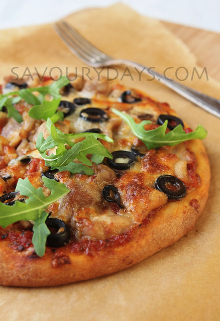 Pizza with chicken, mushroom, olive, mozzarella cheese, tomato sauce & fresh rucola