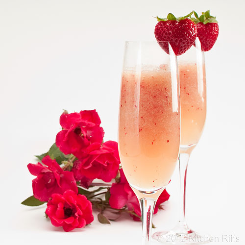 Bellini Cocktails with Strawberry Garnish and Roses in Background, on White