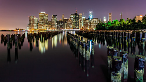 from park city nyc newyorkcity longexposure light newyork seascape reflection tower water brooklyn night skyscraper buildings stars photography lights harbor scenery downtown gallery cityscape image manhattan worldtradecenter fineart lowereastside stock scenic dumbo canvas poop eastriver flare wtc pylons pillars groundzero lowermanhattan starburst piles brooklynbridgepark tower1 freedomtower smoothwater croporama