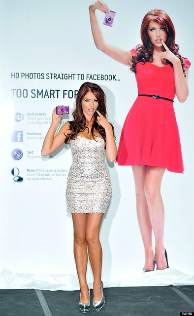 Samsung ad with Amy Childs holding a phone with a vacant expression. The ad says Too Smart for Amy and the real Amy Childs is standing in front of it