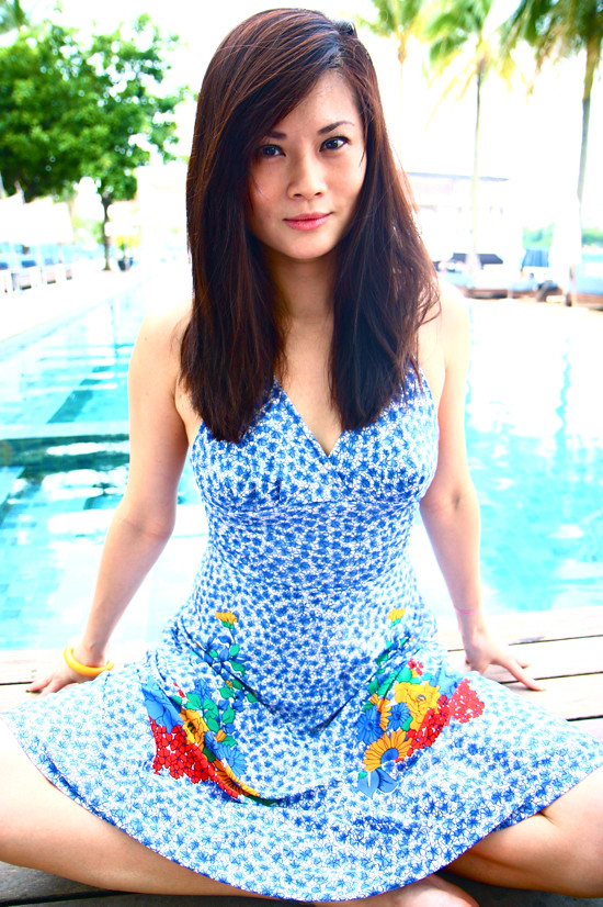 Andrea sizzles by the pool in a 1970s vintage blue halter dress (S/M) with bright floral accents.