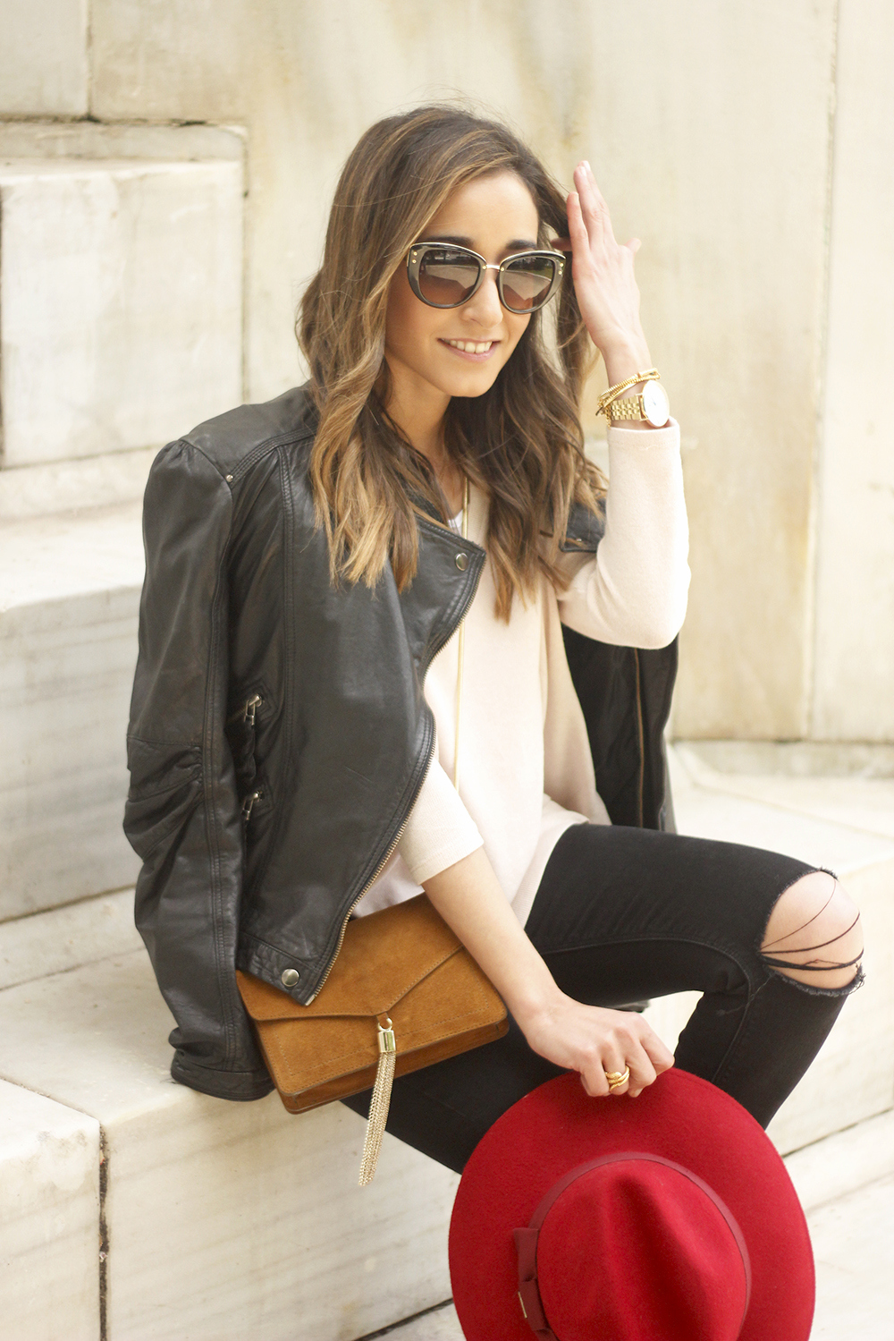 black biker jacket ripped jeans red hat camel bag outfit fashion style spring09