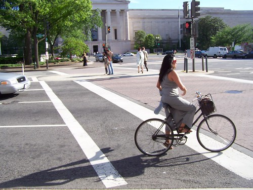 Woman bicycling on Pennsylvania Avenue NW, waiting for the traffic signal