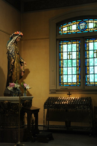 Statue of Mary, stained glass windows with cross, votive candles, flowers, capital, chapel, St. James Cathedral, First Hill, Seattle, Washington, USA by Wonderlane