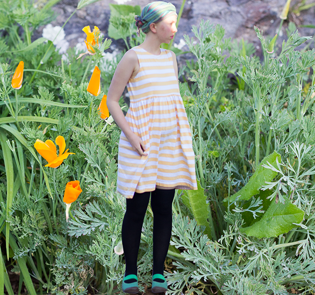 teal headscarf, striped yellow dress, green grass, California poppies