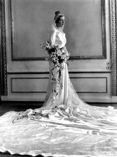 a black and white photo of a bride in a long white dress with a train