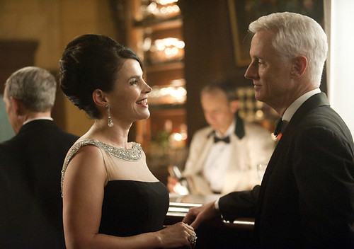 Mme Calvet and Roger Sterling standing together in front of the bar