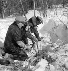 A trapper and his brother, Noah, preparing a beaver trap