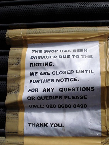 """A piece of white paper taped to a shutter with brown packing tape, printed in black capital letters: """"The shop has been damaged due to the rioting. We are closed until further notice. For any questions or queries please call: 020 8680 8490. Thank you."""""""