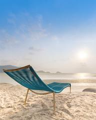 Beach chair on a tropical beach during sunset. - Shallow of focus