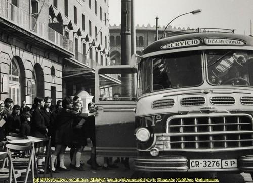 Barcelona, un grupo de niñas, junto a un autocar en la plaza de España. by Octavi Centelles