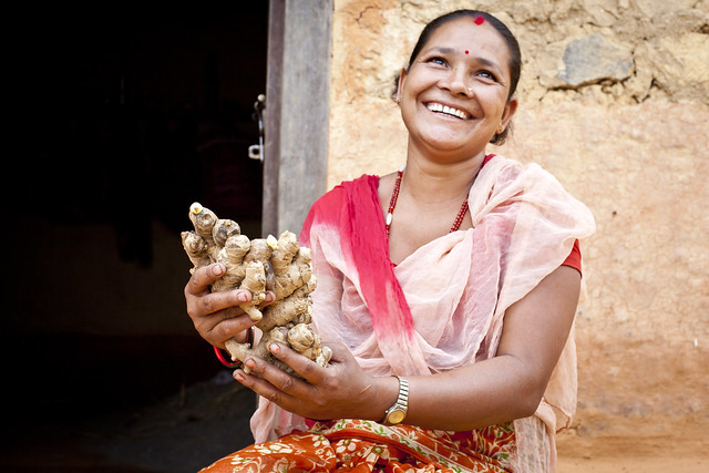 A woman smiles as she holds ginger roots in her hands.